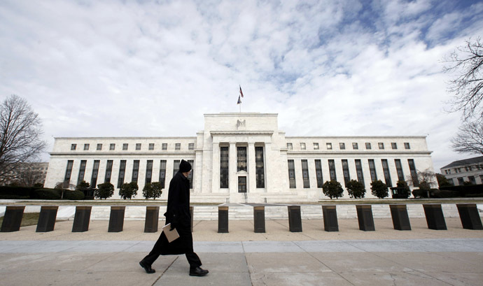 A pedestrian passes the Federal Reserve Building  in Washington